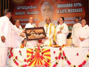 9. BK Lakshmiji presenting the Godly gift to Prof. K. Keshava Murthy